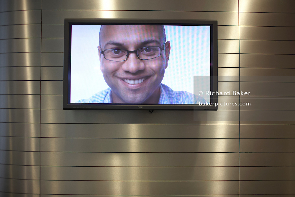 TV screen displaying corporate greeting smiley face at main entrance of an auditing company's London headquarters