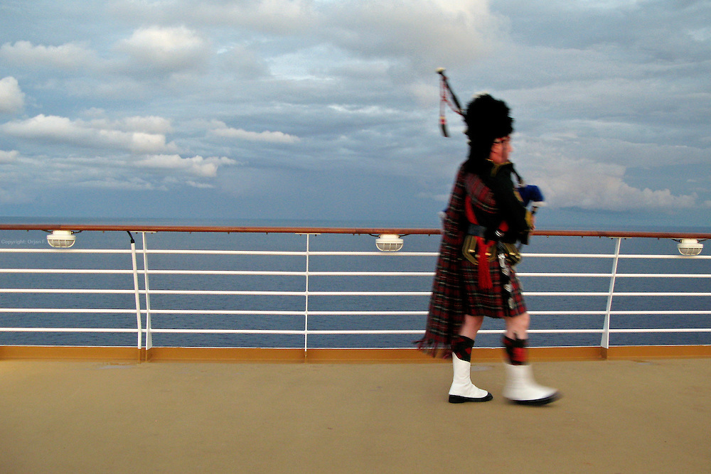 A bagpiper in full regalia plays at sunset onboard the cruise ship Oasis of the Seas. The ship, currently the largest in the world, is owned by Royal Carribean Cruise Line.