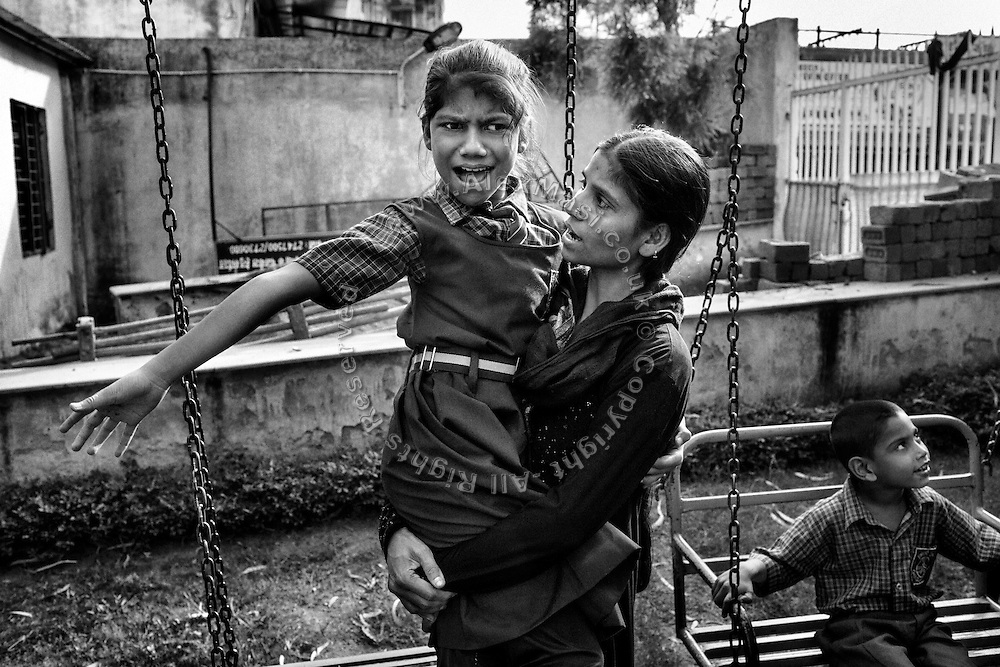 Parveen Khan, 34, a '1984 Gas Survivor', is holding her disabled daughter Misba Khan, 10, a girl affected by cerebral palsy, while in the garden of Chingari Trust Rehabilitation Centre in Bhopal, Madhya Pradesh, India, near the abandoned Union Carbide (now DOW Chemical) industrial complex.