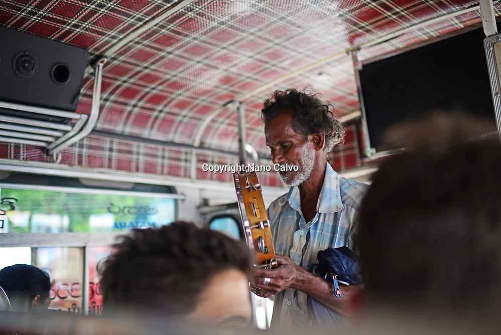 Ambulant musician playing tambourine inside a bus, Sri Lanka