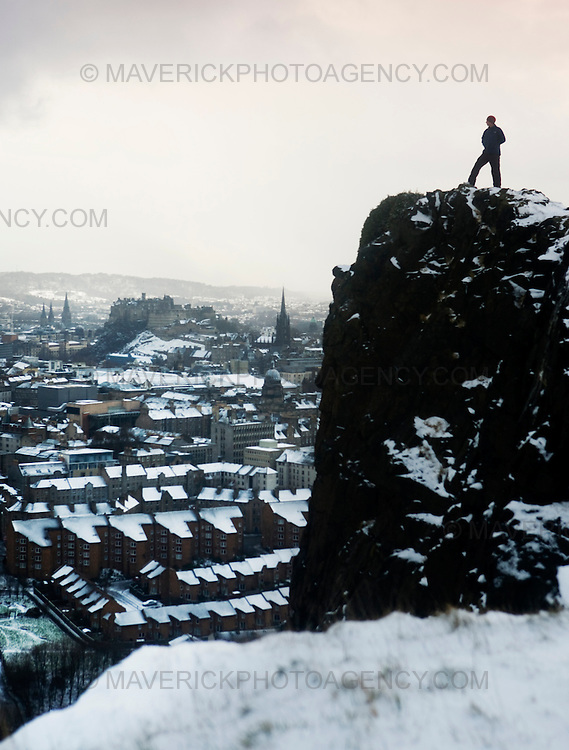A man walks across the Edinburgh 'Crags' with a snow covered Edinburgh city behind..02/2/2009.Picture Michael Hughes/Maverick