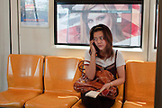 Mar 25, 2009 -- BANGKOK, THAILAND: A woman talks on her cell phone on the BTS, the Bangkok Sky Train, a commuter train. Photo by Jack Kurtz