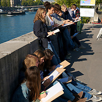Young art students sketching near the Seine River.