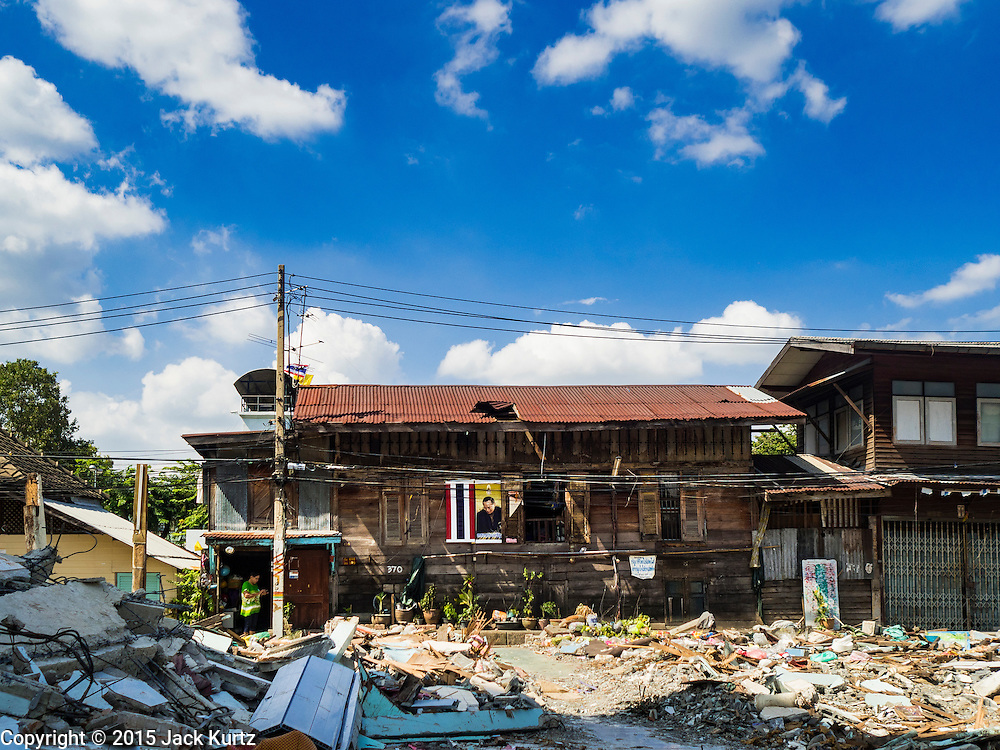 27 NOVEMBER 2015 - BANGKOK, THAILAND:  A woman stands in the doorway of her home, one of the only still standing homes in the Wat Kalayanamit neighborhood. Fifty-four homes around Wat Kalayanamit, a historic Buddhist temple on the Chao Phraya River in the Thonburi section of Bangkok, are being razed and the residents evicted to make way for new development at the temple. The abbot of the temple said he was evicting the residents, who have lived on the temple grounds for generations, because their homes are unsafe and because he wants to improve the temple grounds. The evictions are a part of a Bangkok trend, especially along the Chao Phraya River and BTS light rail lines. Low income people are being evicted from their long time homes to make way for urban renewal.             PHOTO BY JACK KURTZ