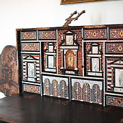SINTRA, Portugal - A 17th-century Spanish cabinet with detailed inlay work. The Palace of Sintra (Palácio Nacional de Sintra) is a mediaeval royal palace in Sintra and part of the UNESCO World Heritage Site that encompasses several sites in and around Sintra, just outside Lisbon. The palace dates to at least the early 15th century and was at its peak during the 15th and 16th centuries. It remains one of the best-preserved royal residences in Portugal.