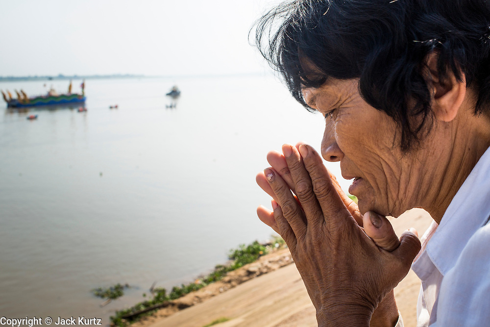 "05 FEBRUARY 2013 - PHNOM PENH, CAMBODIA: A Cambodian woman prays as the Royal Barge carrying the ashes of King-Father Norodom Sihanouk heads up the Mekong River to scatter the revered King's ashes. Sihanouk's ashes will be scattered in locations across Cambodia. Tuesday, they were scattered on the Mekong River. Norodom Sihanouk (31 October 1922 - 15 October 2012) was the King of Cambodia from 1941 to 1955 and again from 1993 to 2004. He was the effective ruler of Cambodia from 1953 to 1970. After his second abdication in 2004, he was given the honorific of ""The King-Father of Cambodia."" Sihanouk died in Beijing, China, where he was receiving medical care, on Oct. 15, 2012.    PHOTO BY JACK KURTZ"