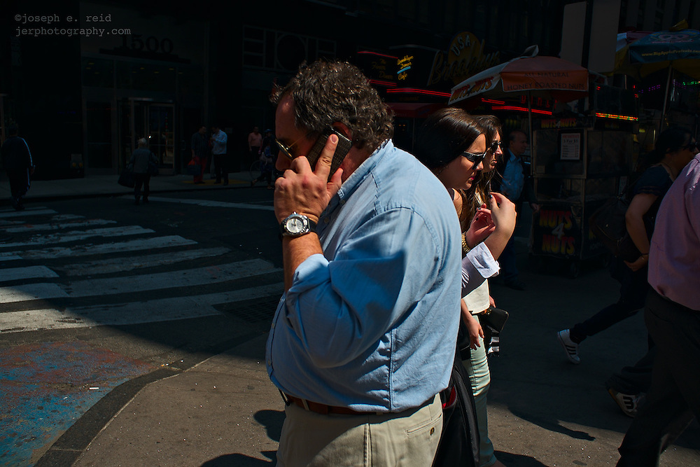 Man using cell phone passing two women in sunglasses
