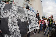 Pilgrims at a vigil for martyred Archbishop Oscar Romero unfurl a painted banner outside San Salvador's Metropolitan Cathedral. The banner drawings depict Romero's steadfast love and support for the poor and campesino farm workers. El Salvador prepares for the beatification ceremony and mass announcing the beatification of Archbishop Oscar Romero. The Archbishop was slain at the alter of his Church of the Divine Providence by a right wing gunman in 1980. Oscar Arnulfo Romero y Galdamez became the fourth Archbishop of San Salvador, succeeding Luis Chavez, and spoke out against poverty, social injustice, assassinations and torture. Romero was assassinated while offering Mass on March 24, 1980.