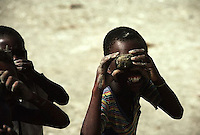 1986, Haiti --- Young boys smile as they look at the photographer through toy cameras they have made from clay. --- Image by © Owen Franken/CORBIS