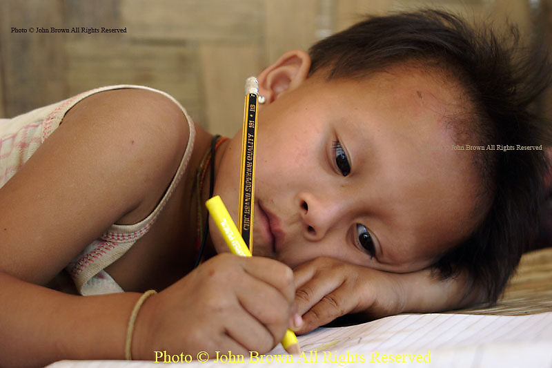 A young Karen Paduang refugee boy displays his artistic talent at his home in Ban Nai Soi, Thailand.  The Karen people fled Burma (Myanmar) to escape from war atrocities and are considered a tourist attraction by the Thai government...
