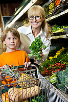 Portrait of a happy woman showing vegetable with grandson holding shopping cart in market
