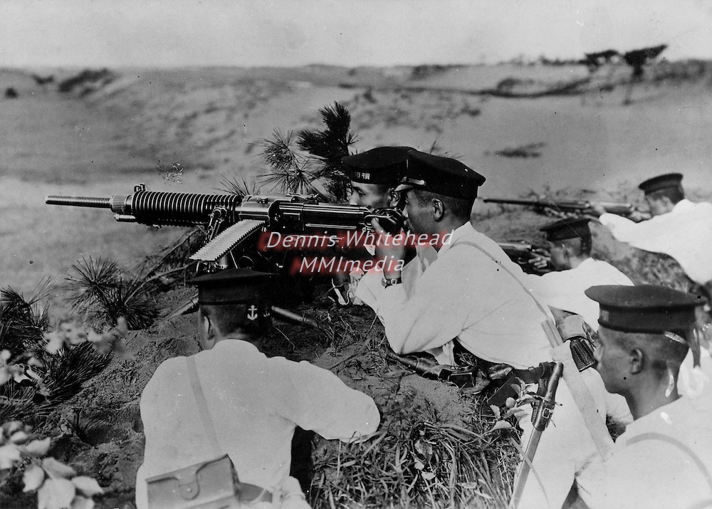 Photograph captured by U.S. Marines on Guadalcanal Island showing Japanese sailors wearing white uniforms and dress caps, posed behind a heavy machine gun.