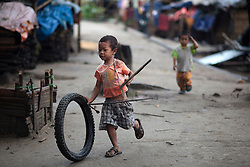 A kid play with a tire in Je Yang Internal Displacement People refugee camp in Laiza village close to the China border, Myanmar on August 1, 2012. This is the biggest IDP camp in Laiza with 6847 refugees according to KIO (Kachin Independence Organization) on 24 July, 2012, also according to the same source around 50000 Kachin people live as refugees in those camps.