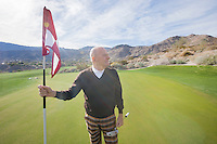 Senior male golfer looking away while holding flag and putter at golf course