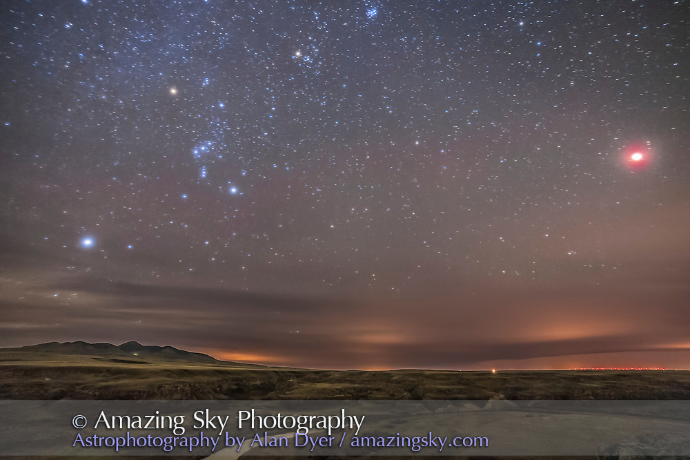The eclipsed Moon, October 8, 2014, over the Milk River and Writing-on-Stone Provincial Park in Alberta, with the Sweetgrass Hills of Montana to the south at left. The Moon was in total eclipse when I took this, and shines at right as a bright red glow. Lights from Coutts and towns in Montana light the clouds on the horizon. Orion and the winter stars stand at left, with Sirius at far left and Aldebaran and the Pleiades at top centre. The buildings in the valley below are the old NWMP outpost buildings from the late 1800s. The night was partly cloudy and hazy, thus the glows around stars and the Moon. <br /> <br /> This is a 1-minute exposure at f/2.8 with the 14mm Rokinon lens and Canon 6D at ISO 6400. The ground however is from a stack of 5 x 1 minute exposures to smooth noise.