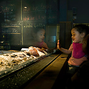 A young girl looks at the oysters on ice at the raw bar at Kushi, an Izakaya and Sushi restaurant in downtown Washington, DC.