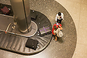"Seen from an aerial walkway, we look down on a lady airline passenger being helped to pull her heavy suitacse from the carousel in the baggage reclaim hall in the arrivals of Heathrow Airport's Terminal 5. 50-70,000 pieces of British Airways baggage a day travel through 11 miles of conveyor belts which were installed in a 5-storey underground hall beneath the 400m (a quarter of a mile) length of Terminal 5. T5 alone has the capacity to serve around 30 million passengers a year and was completed in 2008 at a cost of £4.3bn. The system was designed by an integrated team from the airport operator BAA, BA and Vanderlande Industries of the Netherlands, and handles both intra-terminal and inter-terminal luggage. From writer Alain de Botton's book project ""A Week at the Airport: A Heathrow Diary"" (2009)."