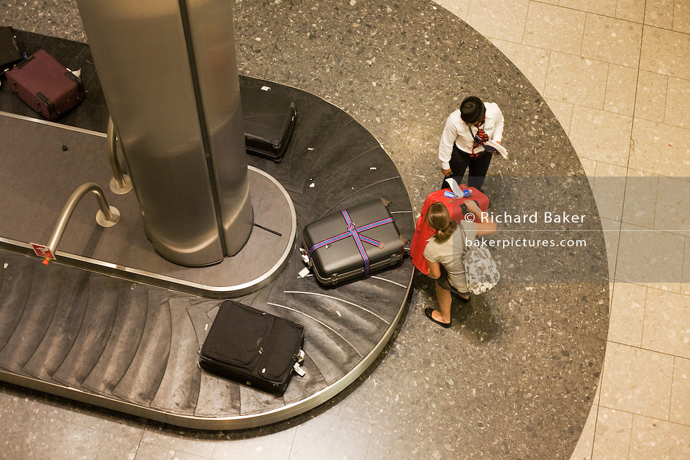 """Seen from an aerial walkway, we look down on a lady airline passenger being helped to pull her heavy suitacse from the carousel in the baggage reclaim hall in the arrivals of Heathrow Airport's Terminal 5. 50-70,000 pieces of British Airways baggage a day travel through 11 miles of conveyor belts which were installed in a 5-storey underground hall beneath the 400m (a quarter of a mile) length of Terminal 5. T5 alone has the capacity to serve around 30 million passengers a year and was completed in 2008 at a cost of £4.3bn. The system was designed by an integrated team from the airport operator BAA, BA and Vanderlande Industries of the Netherlands, and handles both intra-terminal and inter-terminal luggage. From writer Alain de Botton's book project """"A Week at the Airport: A Heathrow Diary"""" (2009)."""