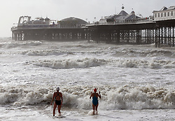 Two swimmer's  brave the rough seas on the beach at Brighton as the south coast braces itself for the storm, Sunday, 27th October 2013. Picture by Stephen Lock / i-Images