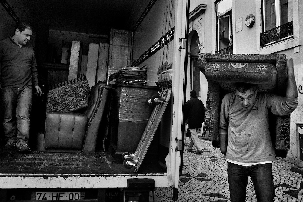 A man carries an armchair over his head while moving furnishings from an apartment of an elderly person who died few days before, at Martim Moniz neighborhood, in central Lisbon, Portugal, on November 21, 2012. Portugal is on the top EU country list in inequality and social contrast. Poverty rates on elderly community is nowadays in 21%, and Lisbon itself has increased 80% over the past 20 years. Due to the financial crisis, the number of retired people on food distribution centers increases weekly while austerity measures recently announced by the government has affected dozens of social institutions. Data released on Sunday by the WHO (World Health Organization) indicates that 39.4% of elderly people in Portugal are victims of abuse and, of these, 32.9% are victims of psychological abuse, 16.5% of racketeering, 12.8% of violation of their rights, 9.9% of negligence, 3.6% of sexual abuse and 2.8% of physical abuse. Still, from a WHO research, in Portugal, 44% of households with a person aged over 65 years have financial difficulties in keeping the home adequately heated. Photo by Mauricio Lima for The New York Times