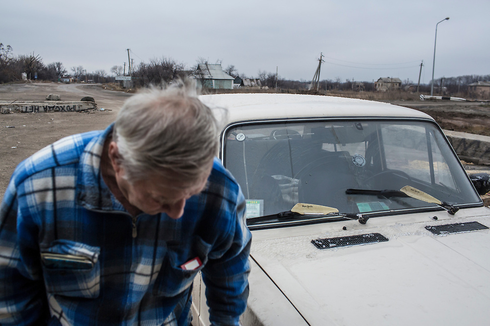 PERVOMAISKE, UKRAINE - NOVEMBER 18, 2014: A man traveling with his wife to their home in the town of Ilovaisk cleans ice off his car while attempting to pass a checkpoint guarded by the 5th platoon of the Dnipro-1 brigade, a pro-Ukraine militia, in Pervomaiske, Ukraine. CREDIT: Brendan Hoffman for The New York Times