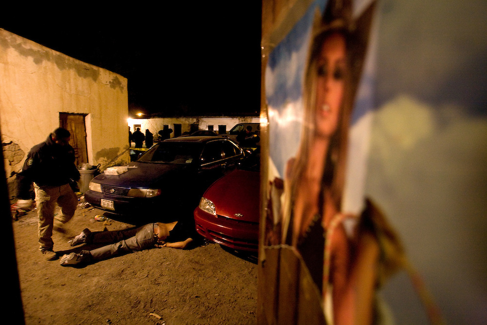 Mexican investigators work in the scene of an assassination a man out side of a small bar in Juarez Mexico .Locals witness say that the assassinators call the man out, ?they didn?t want to kill all the people in the bar? they said..Sunday December 21,2008