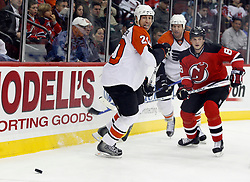 November 8, 2007; Newark, NJ, USA;  Philadelphia Flyers center R.J. Umberger (20) plays the puck away from New Jersey Devils defenseman Sheldon Brookbank (8) during the first period at the Prudential Center in Newark, NJ.