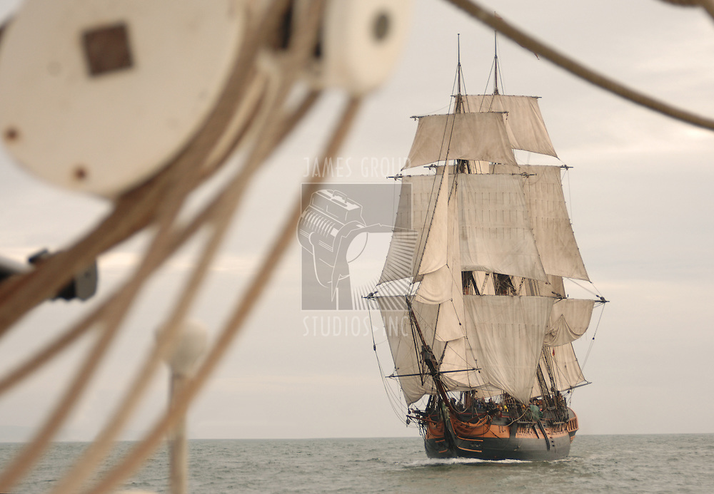 Vintage frigate viewed throught the rigging of another ship