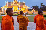 02 FEBRUARY 2013 - PHNOM PENH, CAMBODIA:  A Buddhist monk stands on Sisowath Quay, Phnom Penh's riverfront boulevard, to photograph the Royal Palace. Much of Phnom Penh has been shut down to honor former King Norodom Sihanouk, who ruled Cambodia from independence in 1953 until he was overthrown by a military coup in 1970. Only bars, restaurants and hotels that cater to foreign tourists are supposed to be open. The only music being played publicly is classical Khmer music. Sihanouk died in Beijing, China, in October 2012 and will be cremated during a state funeral royal ceremony on Monday, Feb. 4.    PHOTO BY JACK KURTZ