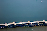 Nederland, Zuid-Holland, Haringvliet, 12-06-2009; Detail Haringvlietsluizen, tussen Voorne-Putten en Goeree-Overflakkee. De sluizen, onderdeel van de Deltawerken, zijn spuisluizen en zorgen er voor dat het zoete water uit het Haringvlie zoals aangevoerd door Maas en Rijn geloosd kan worden. In het kader van modern natuurbeheer  ('getemd getij') gaan de sluizen tegenwoordig bij eb én vloed beperkt open (rechts op de foto), om de getijden hun enigszins terug te laten komen in het estuarium .Dam and sluices between islands Voorne-Putten en Goeree-Overflakkee. The sluices are for draining water coming from the rivers Rhine and Maas (Meuse). Modern ecological insight has led to opening the sluices semi-permanently, resulting in the estuary function of the Haringvliet patially being restored.Swart collectie, luchtfoto (25 procent toeslag); Swart Collection, aerial photo (additional fee required).foto Siebe Swart / photo Siebe Swart