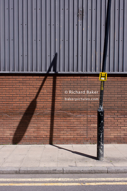 Leaning post and its own shadow on a brick wall in south London. In an urban landscape of angles and diagonals, we see the bent nature of vertical upright lines against the straight parallels of corugated wall sheeting, showing the random, off-true setting of the lamppost, in a side street in Southwark, south London.