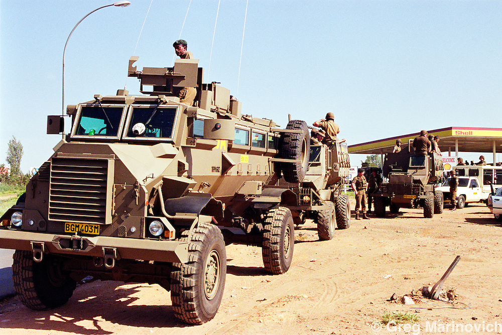 Meadowlands, Soweto, Johannesburg, South Africa. Military vehicles watch during a clash between ANC and IFP.  26 April 1992