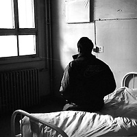 BEIJING, 2000 : an anonymous HIV infected patient sitting on his bed inside the HIV ward of the You'an hospital in Beijing..As Aids is considered a shameful disease in China and officially it's transmitted only through prostitutes and drug users, most people do not wish to have their identity revealed. In fact, in China HIV is transmitted in most cases through bad blood donations in the countryside....