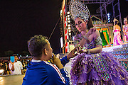 23 NOVEMBER 2013 - BANGKOK, THAILAND:  A performer with the Prathom Bunteung Silp mor lam troupe greets a fan during a performance in Bangkok. Although the show is scripted, performers leave their place in the show to go down and greet fans throughout the show. Mor Lam is a traditional Lao form of song in Laos and Isan (northeast Thailand). It is sometimes compared to American country music, song usually revolve around unrequited love, mor lam and the complexities of rural life. Mor Lam shows are an important part of festivals and fairs in rural Thailand. Mor lam has become very popular in Isan migrant communities in Bangkok. Once performed by bands and singers, live performances are now spectacles, involving several singers, a dance troupe and comedians. The dancers (or hang khreuang) in particular often wear fancy costumes, and singers go through several costume changes in the course of a performance. Prathom Bunteung Silp is one of the best known Mor Lam troupes in Thailand with more than 250 performers and a total crew of almost 300 people. The troupe has been performing for more 55 years. It forms every August and performs through June then breaks for the rainy season.                PHOTO BY JACK KURTZ