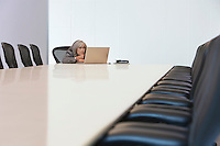 Business woman using laptop in board room