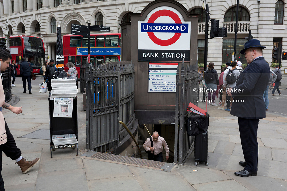 A businessman uses his mobile phone outside the entrance of Bank Underground Station at the corner of King William Street in the City of London, on 30th May 2018, in London, England.