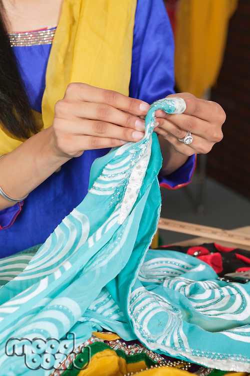 Midsection of dressmaker working on a sari