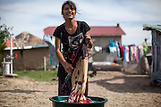 "A young woman washes laundry in the open air in Frumuşani. Drop out rates from education for young Roma students are still high. ""Better access to schools and improving educational outcomes are key,"" explains Costel Bercus, of the Roma Education Fund."