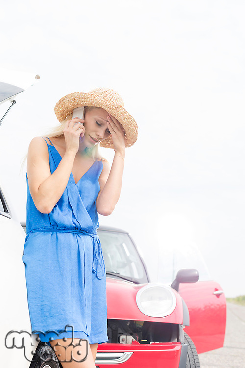 Tensed young woman using cell phone by broken down cars