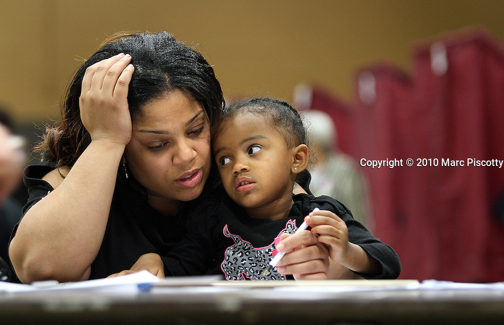 "DENVER, CO - NOVEMBER 2: Samoine Chapman (left) of Denver, Co. pauses to think as she votes with her daughter Giada Chapman, 3, at The Potter's House Church in Denver, Co. The church is located in unincorporated Arapahoe County and the county as a whole is traditionally a conservative area although during the last election the county was carried by the Democrats. It is considered a bellweather county by most and will likely end up playing a pivotal role in which direction the state ends up voting. Chapman said it's the second time she has brought her daughter to the polling place hoping to teach her all about the voting process. She said Giada remarked ""Mommy, I voted for Obama"" as she went through the process this time around. (Photo by Marc Piscotty/ © 2010)"