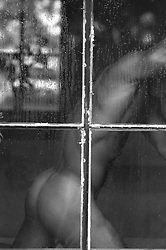 nude man's body standing in a window