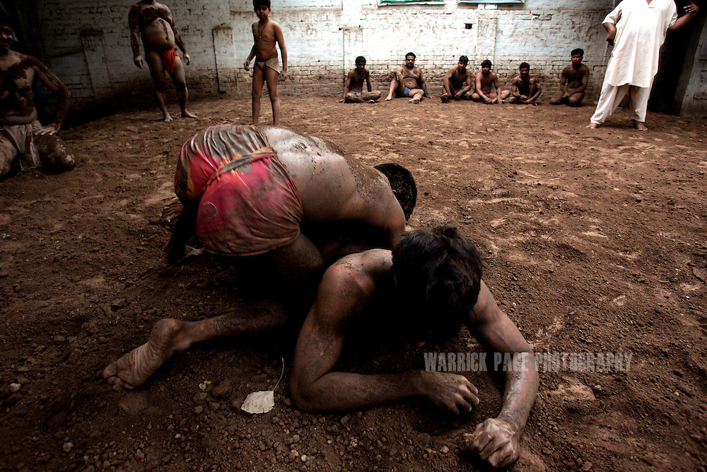 LAHORE, PAKISTAN - JUNE 12: Pehlwanis (wrestlers) practice their fighting techniques at a local training pit, June 12, 2006, in Lahore, Pakistan. Pehlwani is a Persian form of wrestling brought into South Asia by the Mughals, dating back to the 5th century BC but it's popularity is dying in Pakistan due to a lack of funding and interest from the government. Decades ago, hundreds of men would be in constant training, now only dozens remain committed to the ancient sport, attempting to balance daily needs with the strict routine required of a pehlwani. (Photo by Warrick Page)