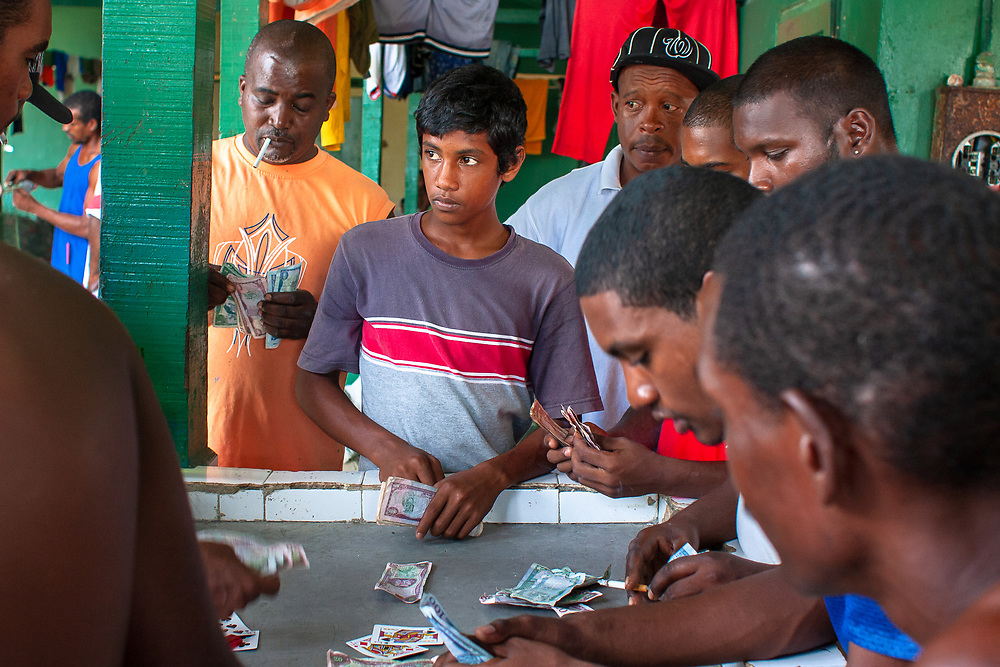 Maracas Bay, Trinidad: After preparing and selling the day's catch, fishermen gamble at wapee, based on the English card game of all fours.