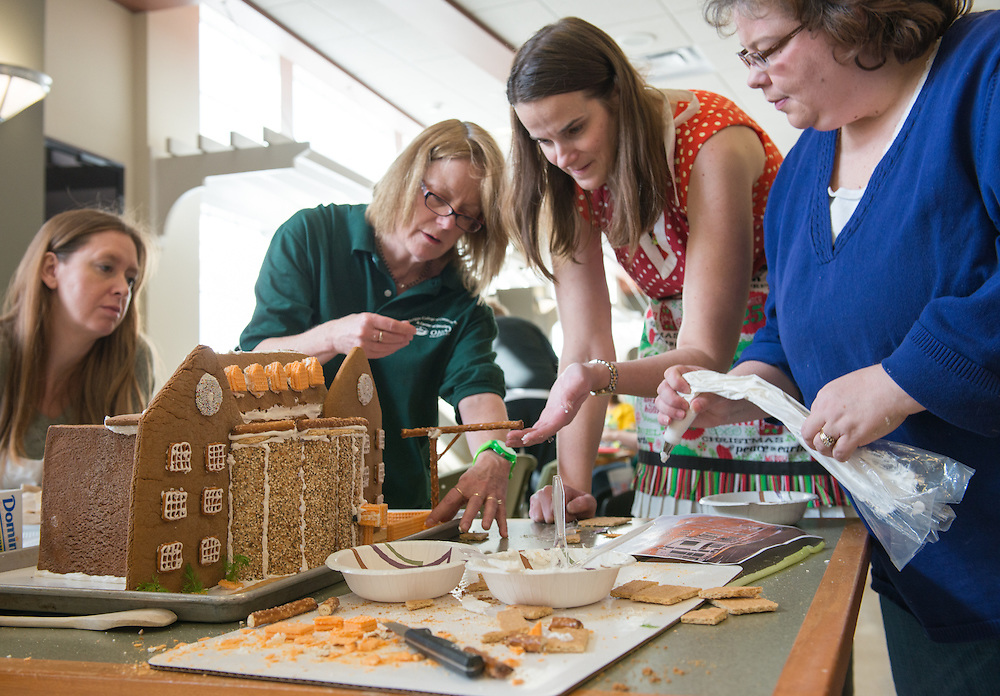 Cindy Smith, Beth Novak and Heather Krugman decorate the entry into the Gingerbread House Decoration Contest. Photo by Ben Siegel