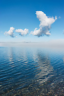 Fog clearing from tranquil surface of lake to reveal blue water under blue sky, Yellowstone Lake, WY, © 2005 David A. Ponton