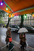 Two women walk beneath coloured lights during damp, gloomy weather in central London.