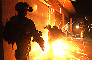 MIDNIGHT RAID.Sparks fly as Soldiers from Charlie Company, 5th Battalion, 20th Infantry Regiment, 3rd Brigade, 2nd ID, use a power saw to cut through a metal door while executing a building search in Samarra, Iraq as part of Operation Arrowhead Blizzard on December, 17 2003. They were looking for Saddam Loyalist and weapon caches. (Alan Lessig/Army Times)