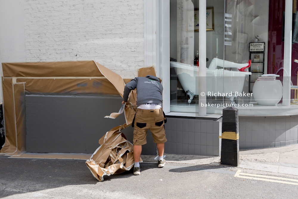 A workman peels off fresh wrapping outside a Mayfair shop retailer, on 5th June 2019, in London, England.