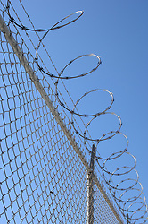 chain link fence with barbed wire against blue sky