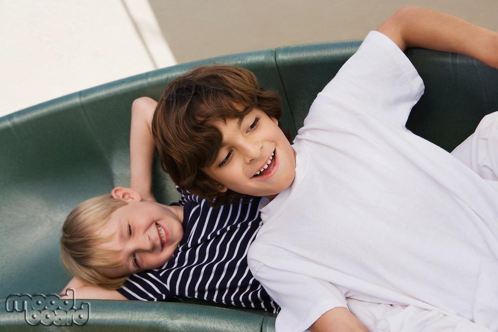 Little Boys Sliding down a Slide